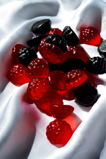 red and blue candy in the shape of berries on white silk