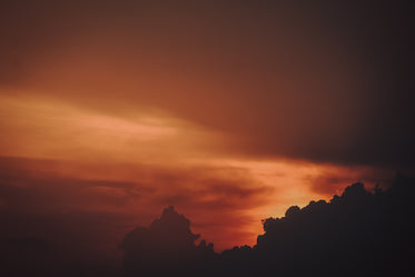 red and orange sky at sunset silhouetting clouds