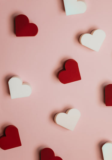 red and white hearts scattered on pink surface