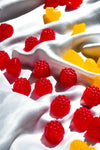 red berry shaped candy on white silk fabric