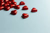 red foiled hearts lay on a light blue background