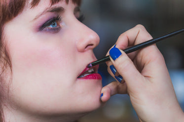 red lipstick being applied with brush