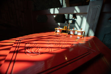 red table with carved inlay is bathed in sunlight