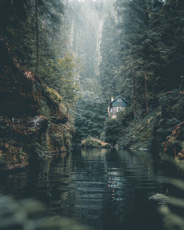 remote log cabin on calm forest river