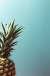 ripe pineapple sits against a blue background