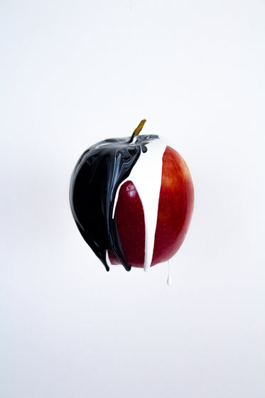 ripe red apple with black and white paint