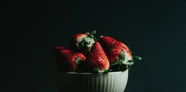 ripe red strawberries in a white bowl