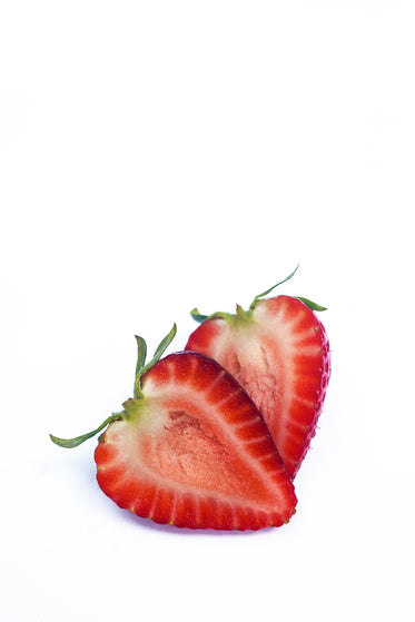 ripe strawberry cut in half on a white surface