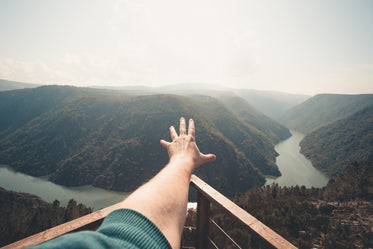 river and hills with a hand reaching outwards
