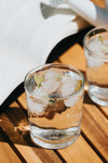 rocks glass with ice and water on a wooden table