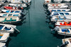 rows of boats in a marina in oily blue water