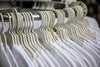 rows of hangers with white t-shirts