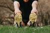 running shoes on green grass of a person stretching