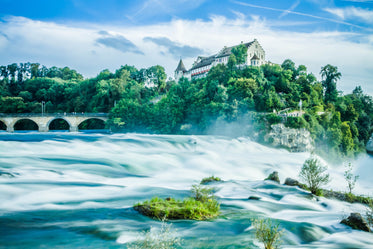 rushing water and rapids beside modern castle
