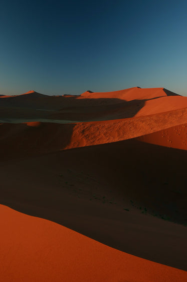 rust colored sand dunes against a deep blue sky