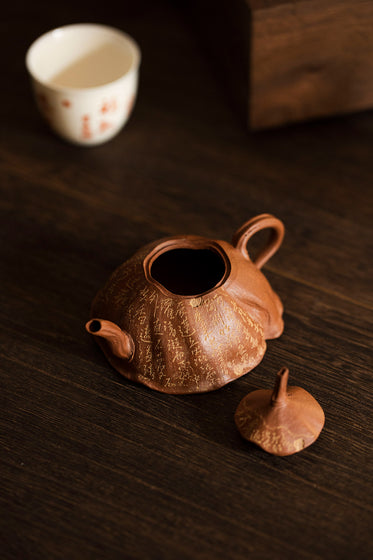 rust colored teapot with its lid of on a wooden table