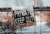 rustic snowy sign reads private keep out