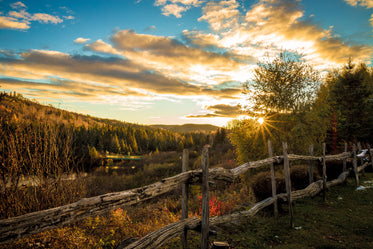 rustic wooden fence surrounding framland at sunset