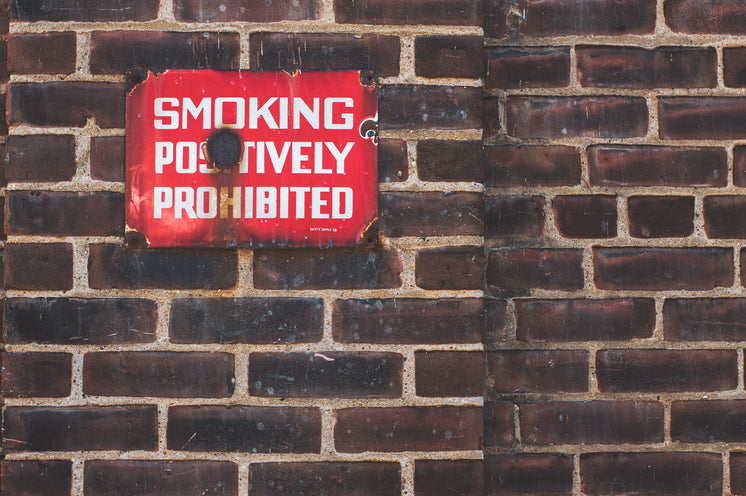 Rusting No Smoking Sign On Brick Wall