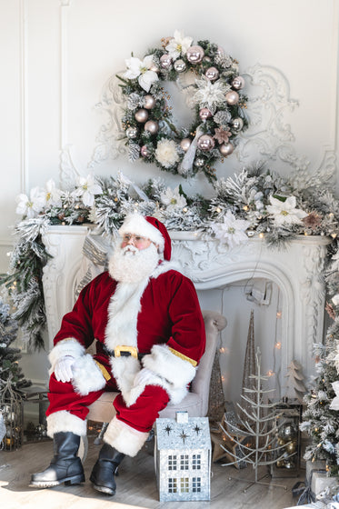 santa sits by the fireplace