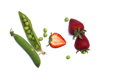 scattered green peas in their pod with strawberries