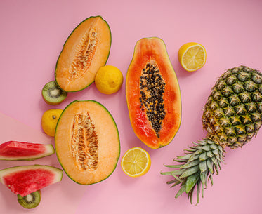 several different fruits lay on a pink background