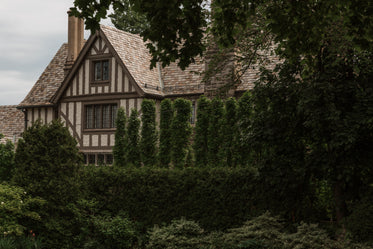 side of a brown house with tall hedges obscuring view