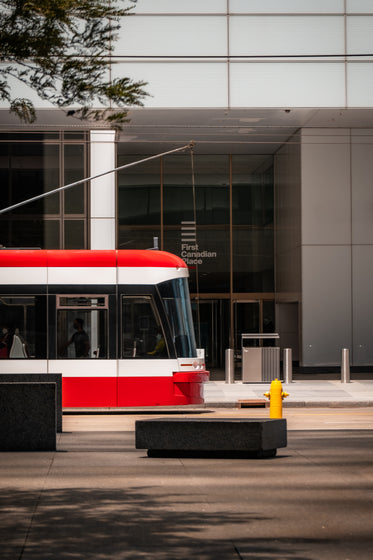 side of a glass building with a red streetcar