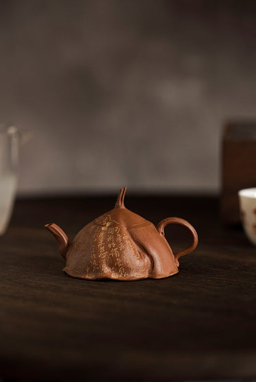 side view of a rust colored teapot