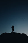 silhouette of a person below crescent moon