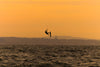 silhouette of a person kite surfing in wavy water