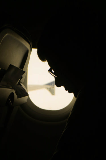 silhouette of a person sitting by an airplane window