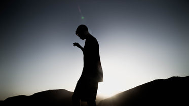 silhouette of a person standing hilly landscape