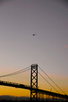 silhouetted large bridge and a helicopter at sunset