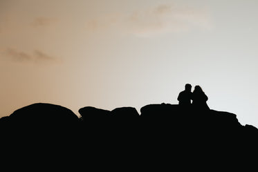 silhouetted people sitting on rocks by the setting sun