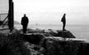 silhouetted people standing by body of water in monochrome
