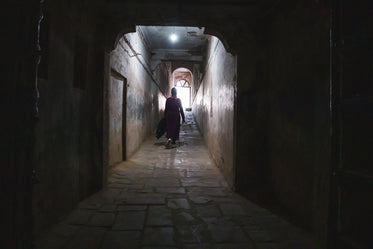 silhouetted person walks down a tunnel