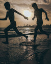 silhouettes of two people splashing on the beach