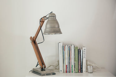 silver lamp on a white table next to books