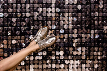 silver wingtip shoes on silver background