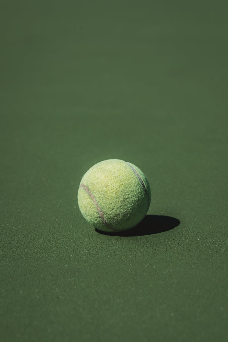 Single Tennis Ball Sits In The Sun On The Court