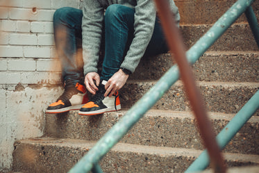 sitting for a moment to tie the laces of fashion sneakers