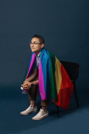 sitting in chair wrapped in pride flag