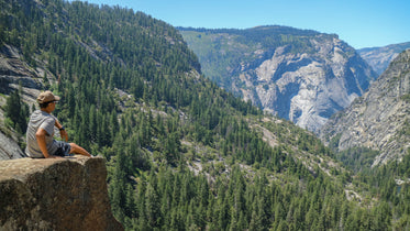 sitting on ledge looking at mountains and trees