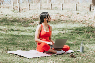 sitting on yoga mat while working on a laptop outdoors