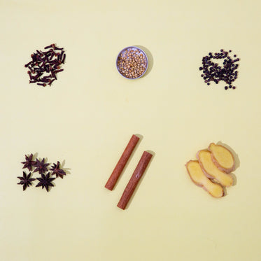 six different spices against a yellow background