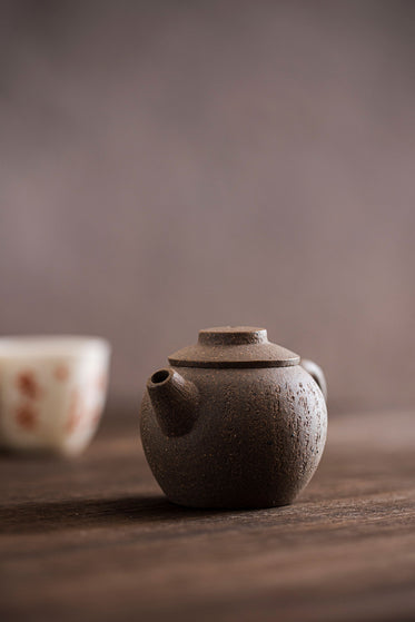 small brown teapot with a white and orange cup behind it