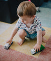 small child squats and plays with toy trucks