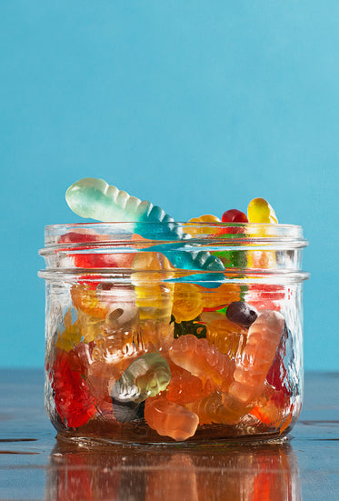 small glass jar filled to the top with gummy worms