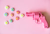 small pink revolver shooting flowers